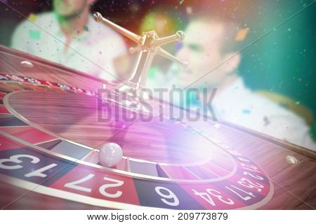 3D image of ball on wooden roulette wheel against group of men watching television in bar