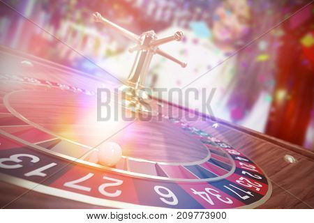 3D image of ball on wooden roulette wheel against pretty bartender pouring tequila into glasses