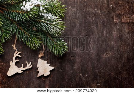 Christmas fir tree and decor over old wooden texture background. Top view with copy space for your greetings