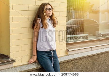 Portrait of a teenage girl 13-14 years old. Urban background