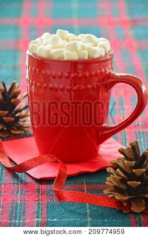 Hot chocolate with marshmallows in festive red mug on tartan background. Vertical format with selective focus on top of mug.