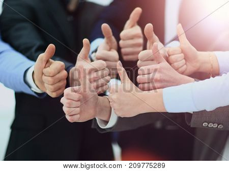 Cheering business people holding many thumbs thumbs up