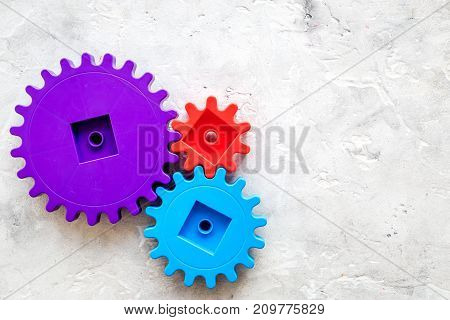 moving forward concept, ideal operating principle with gears and wheels on stone desk background top view mock up