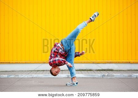 Photo young man hip hop dancer with grunge wall background texture
