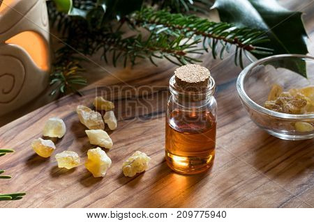 A Bottle Of Frankincense Essential Oil With Frankincense Crystals