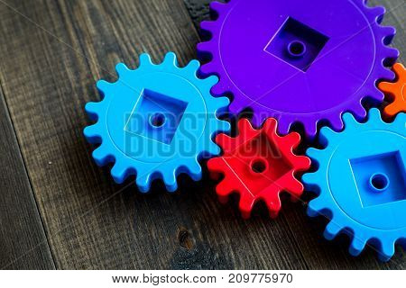 moving forward concept, ideal operating principle with gears and wheels on wooden desk background