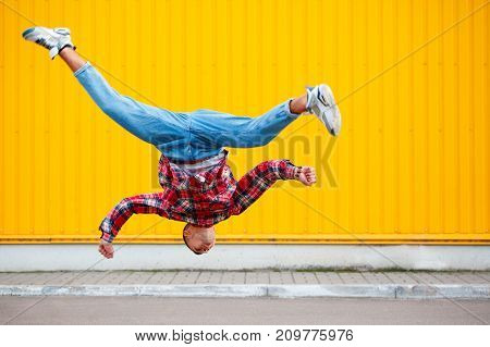 young man hip hop dancer with grunge wall background texture