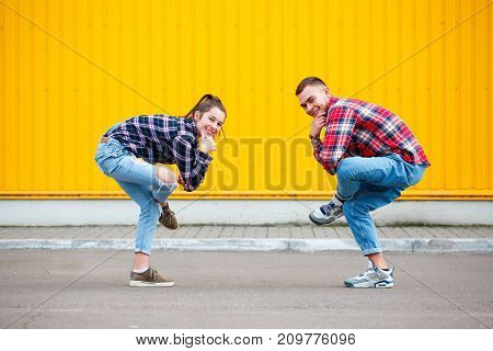 Photoportrait of carefree young couple dancing holding hands in street and smiling, enjoying life