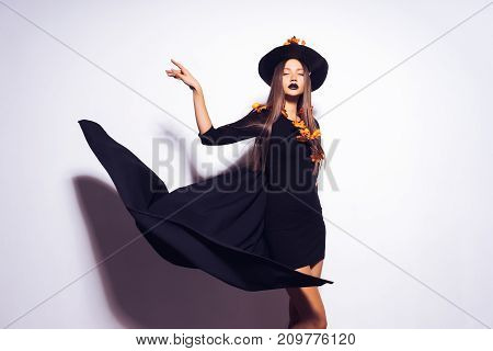 a young sexy gothic girl dressed in a witch for Halloween, in a big black hat and raincoat