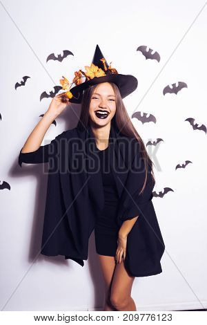 a young sexy gothic girl dressed in a witch for Halloween, in a big black hat adorned with yellow leaves, laughs