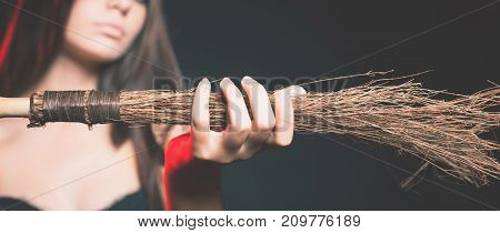 Closeup beautiful woman like witch holding broom. Fashion. Halloween costumes