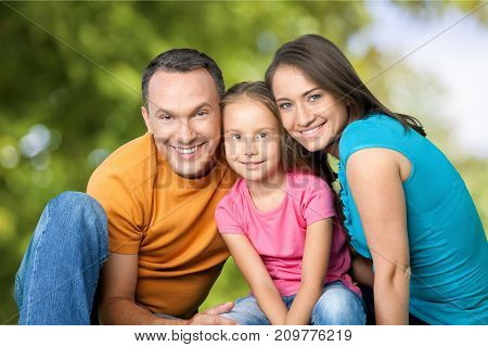 Happy smiling family daughter elementary age pre-adolescent child green