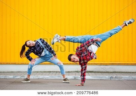Horisontal photo of carefree young couple dancing holding hands on street and enjoying life