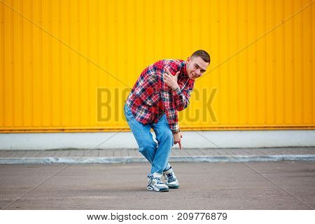 Horisontal photo of young man hip hop dancer with grunge wall background texture