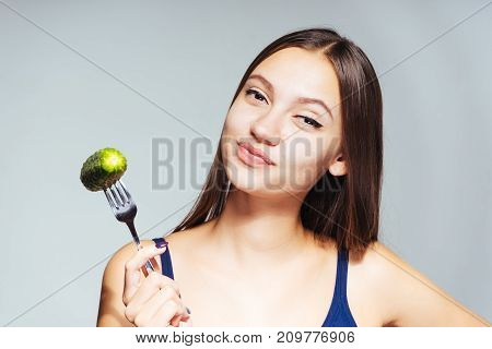 young beautiful sports girl wants to lose weight, eats low-calorie cucumber