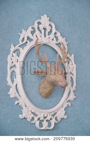 The golden head of a deer in a white openwork frame. Christmas and New Year's decor of the interior