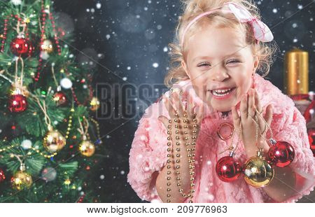 Funny little girl decorating Christmas tree and looking at camera. Garland. New Year 2017. Fairy tale. Dressed in fashion fur coat