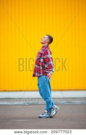 Vertical photo of young man hip hop dancer with grunge wall background texture