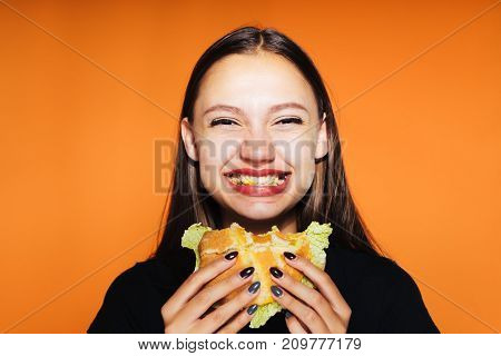 young happy girl wants to lose weight, but eats a calorie harmful burger