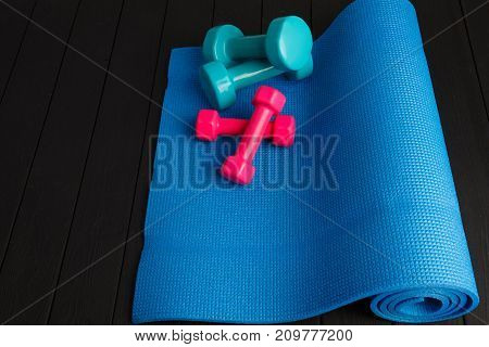 Small pink and big blue dumbbells for sports exercises. Blue gymnastic mat for yoga. Sports equipment on a dark gray wooden parquet. Sport concept.