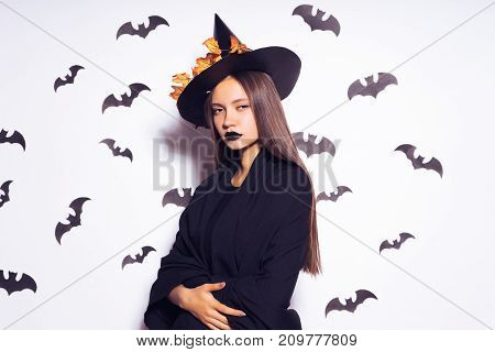 young sexy gothic girl dressed in a witch for Halloween, standing in a big black hat, looks sad
