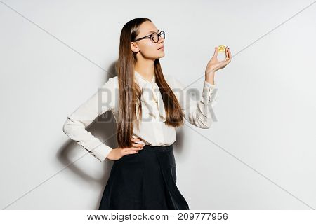 a young modern successful girl with glasses is holding  gold bitcoin