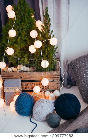 Christmas and New Year decor of the interior. The balls of thread lie on the table in the room