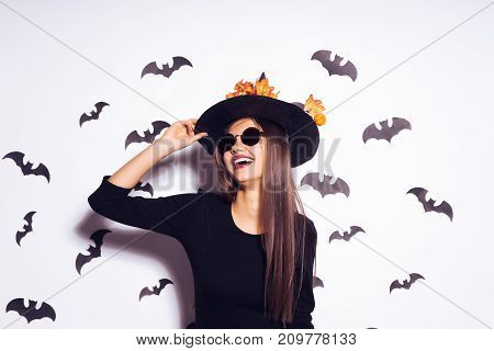 young sexy gothic girl dressed in a witch for Halloween, standing in sunglasses and a big black hat