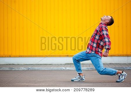 Horisontal portrait of young man hip hop dancer with grunge wall background texture