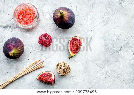 organic cosmetic set with fresh fig, bath salt and scrub on stone table background flat lay mock-up