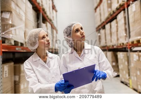 manufacture, industry and people concept - women technologists with clipboard at ice cream factory warehouse