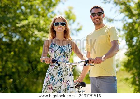 people, leisure and lifestyle concept - happy young couple with bicycle at country