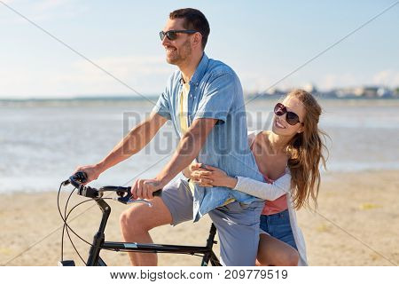 people, leisure and lifestyle concept - happy young couple riding bicycle on beach