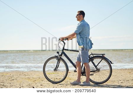 people, leisure and lifestyle concept - happy young man with bicycle on beach