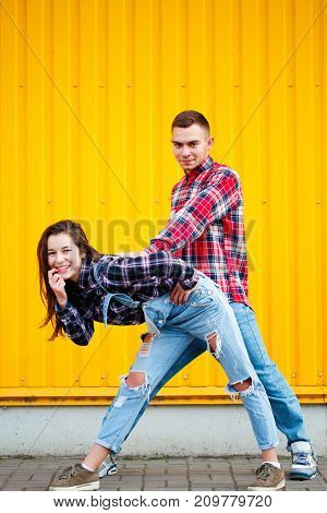 Fine vertical photo of carefree young couple dancing holding hands in street and smiling, enjoying life