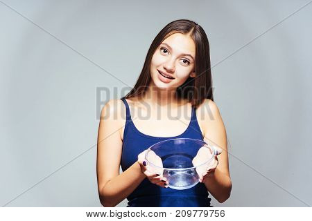 young beautiful sports girl follows wants to lose weight, holds in her hand an empty glass plate