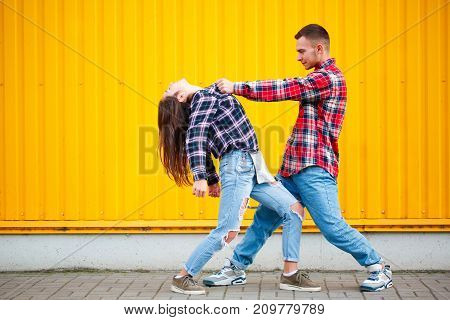 Fine portrait of carefree young couple dancing holding hands in street and smiling
