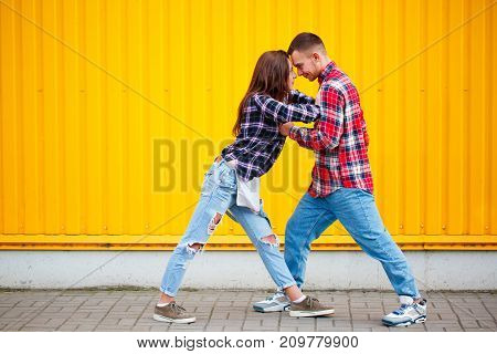 New portrait of carefree young couple dancing holding hands in street and smiling, enjoying life