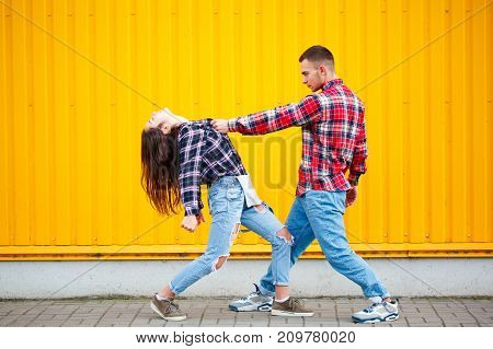 New photo of carefree young couple dancing holding hands in street and smiling, enjoying life