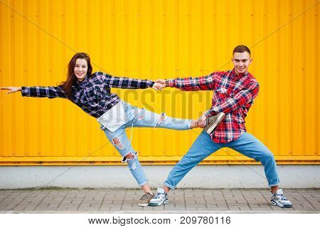 Cool new photo of carefree young couple dancing holding hands in street and smiling, enjoying life. Beloved happy together