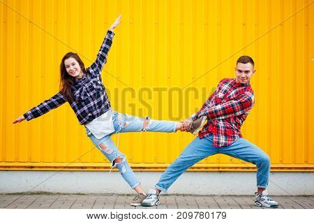 New horisontal portrait of carefree young couple dancing holding hands in street and smiling, enjoying life. Happy together