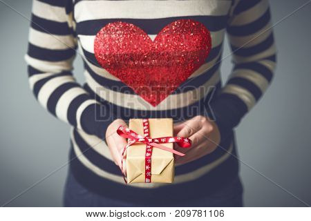 Christmas. A girl in a striped sweater with a red heart on her chest. Girl with a Christmas gift in hands. Gifts for men. Merry Christmas. Knitted mittens. Toned image.