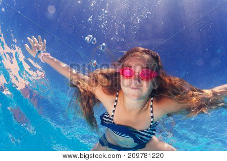 Portrait of preteen girl wearing pink goggles, learning holding breath underwater poster