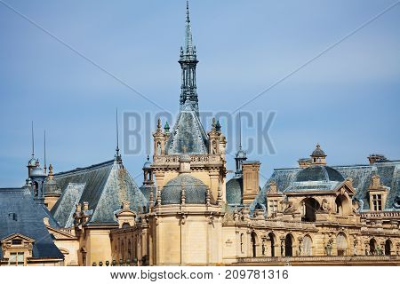 Turrets and cupolas of Chateau de Chantilly castle against blue sky