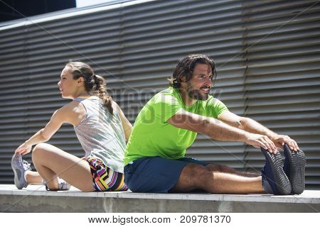 Young Attractive Woman Exercising With A Personal Trainer Outside At Sunny Day