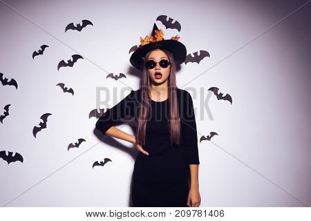 a young sexy gothic girl dressed in a witch for a halloween, in a big black hat and sunglasses, looks surprised