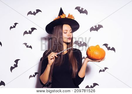 a young sexy gothic girl dressed in a witch for Halloween, in a big black hat, holding a pumpkin and a magic wand