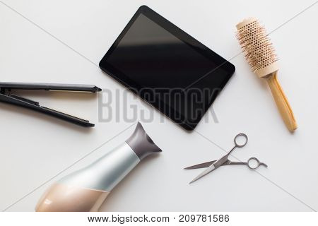 hair tools, beauty and hairdressing concept - tablet pc, scissors, hairdryer with hot styling iron and curling brush on white background