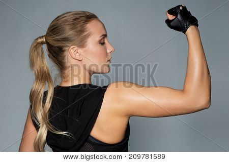 sport, fitness and people concept - close up of young woman posing and showing muscles in gym