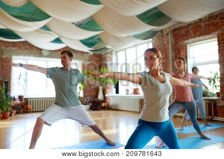 fitness, sport and healthy lifestyle concept - group of people doing yoga in warrior pose at studio